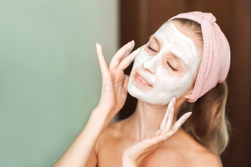 Schoonheidsbehandelingen De jonge vrouw past een masker, room op haar gezichtsclose-up toe Het gezichtsportret van de huidzorg va royalty-vrije stock foto's