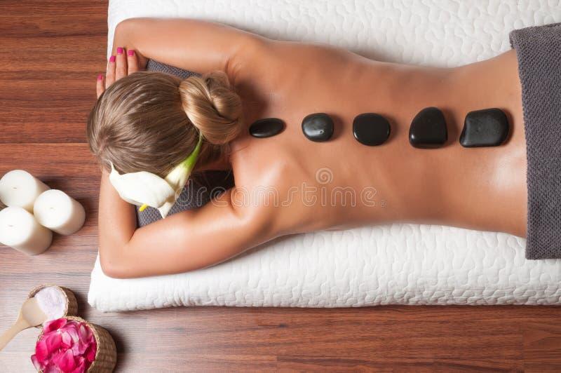 Schoonheidsbehandelingen, een vrouw die bij een gezondheidskuuroord ontspannen terwijl het hebben van een hete steenbehandeling e royalty-vrije stock fotografie
