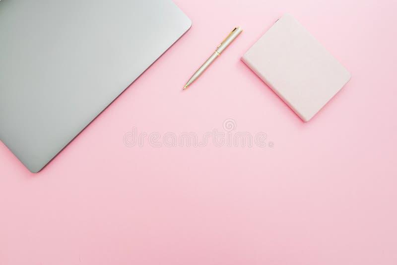 Schoonheidsbureau met laptop, notitieboekje en pen op roze achtergrond Hoogste mening Vlak leg levensstijlconcept stock fotografie
