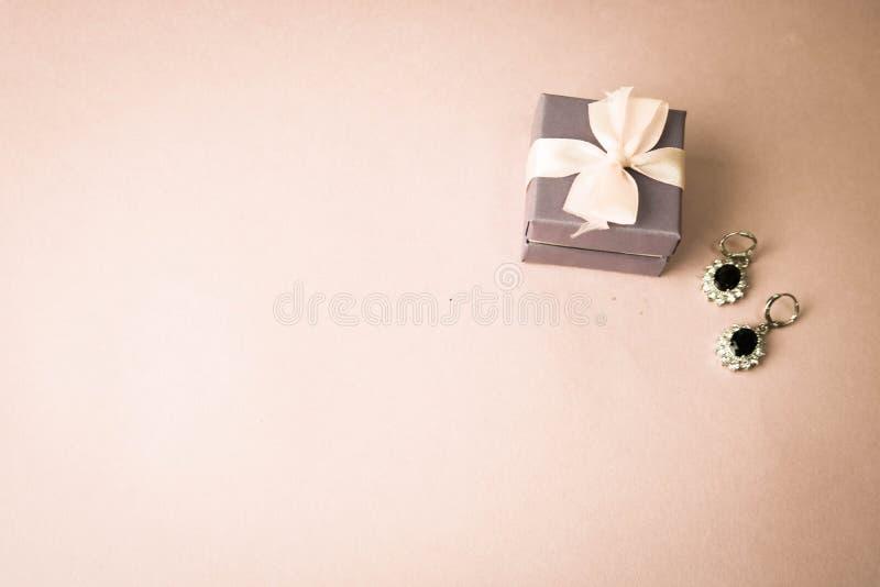 Schoonheidsdoos, feestelijke mooie giftdoos met een boog met zilveren oorringen met edelstenen op een roze purpere achtergrond Vl royalty-vrije stock afbeeldingen
