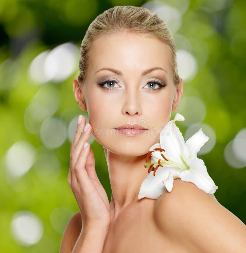 Schoonheidsgezicht van jonge mooie vrouw met bloem royalty-vrije stock afbeeldingen