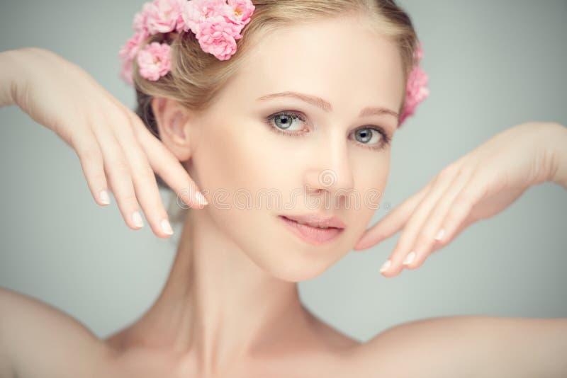 Schoonheidsgezicht van jonge mooie vrouw met roze bloemen royalty-vrije stock afbeeldingen