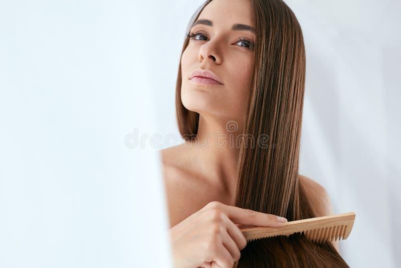 Schoonheidshaarverzorging Mooie Vrouw die Lang Natuurlijk Haar kammen royalty-vrije stock afbeeldingen