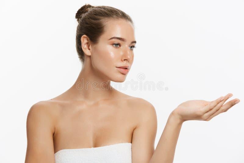 Schoonheidshuid en kuuroordvrouw in handdoek wordt verpakt die copyspace met hand huidig aan kant tonen die Geïsoleerd op wit stock afbeelding