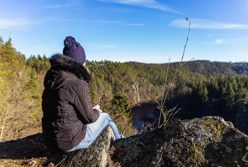 Schoonheidsjonge vrouw die op rots zit met bos en rivier in de vallei stock foto's