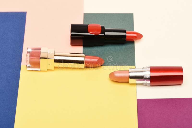Schoonheidslevering, lippenstift, exemplaarruimte Drie rode, scharlaken lippenstiften stock afbeelding