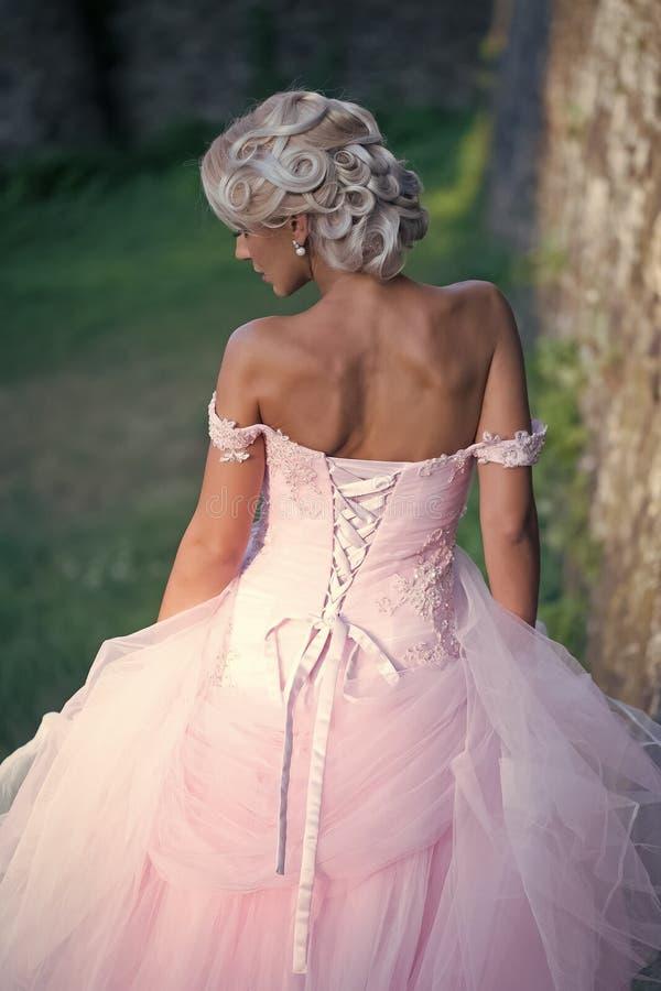 Schoonheidsmannequin Girl De manier ziet eruit Het meisje stelt in roze kleding met open schouders, achtermening stock afbeelding
