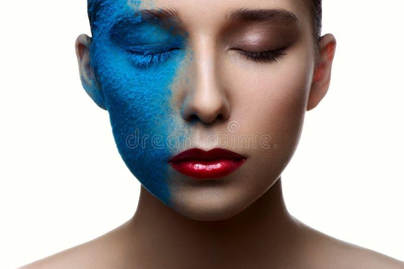 Schoonheidsmeisje met blauw gezicht en rode lippen stock fotografie