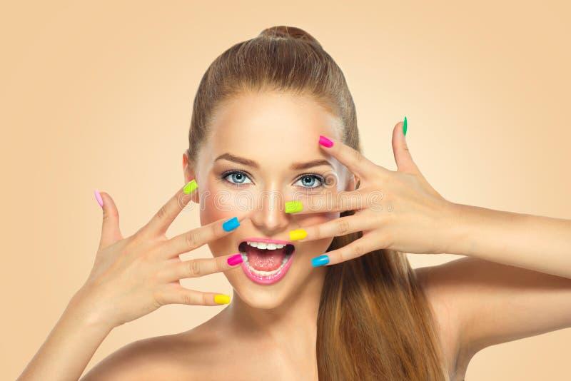 Schoonheidsmeisje met kleurrijk nagellak stock afbeeldingen