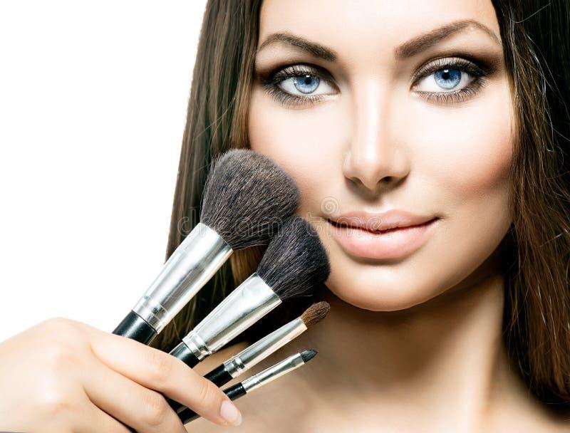 Schoonheidsmeisje met make-upborstels stock afbeeldingen