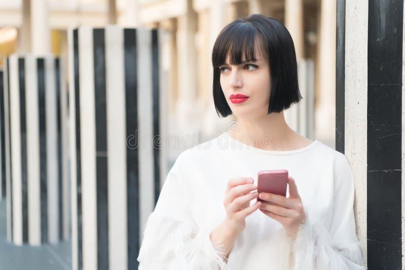 Schoonheidsmeisje met sexy blik in Parijs, Frankrijk Vrouw met rood lippengebruik op smartphone Vrouw met de mobiele telefoon van royalty-vrije stock foto's