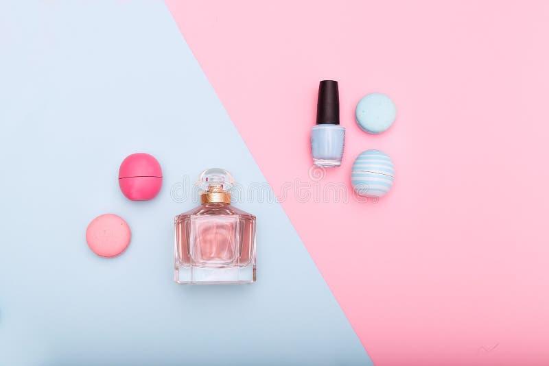 Schoonheidsmiddelen en macarons op blauwe en roze achtergrond royalty-vrije stock foto