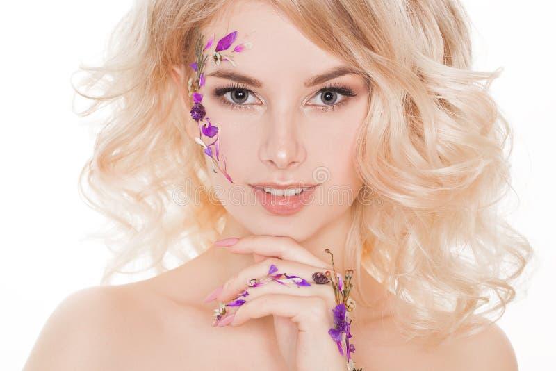 Schoonheidsmiddelen en manicure Close-upportret van aantrekkelijke vrouw met droge bloemen op haar gezicht, pastelkleur van spijk royalty-vrije stock foto's