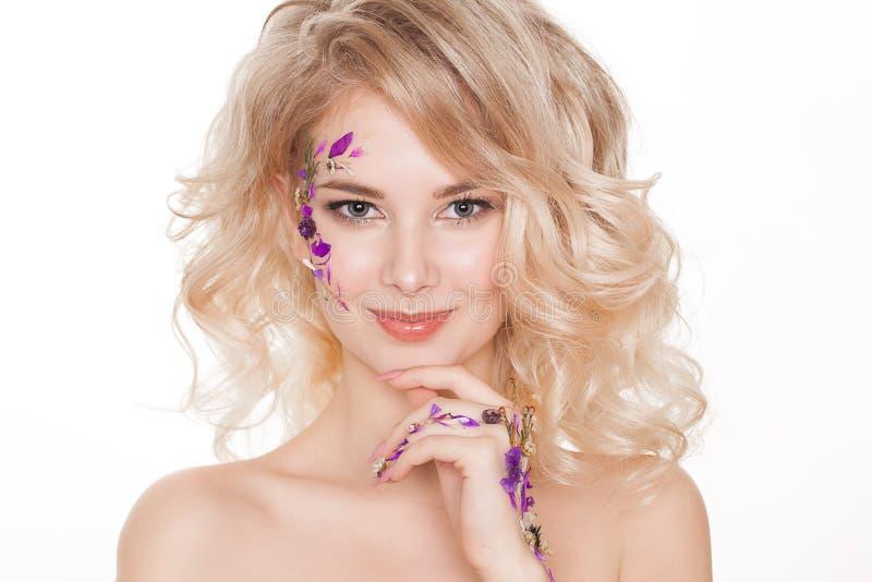 Schoonheidsmiddelen en manicure Close-upportret van aantrekkelijke vrouw met droge bloemen op haar gezicht, pastelkleur van spijk royalty-vrije stock foto