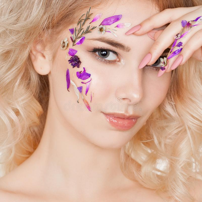 Schoonheidsmiddelen en manicure Close-upportret van aantrekkelijke vrouw met droge bloemen op haar gezicht, pastelkleur van spijk royalty-vrije stock afbeelding
