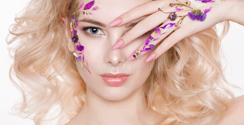 Schoonheidsmiddelen en manicure Close-upportret van aantrekkelijke vrouw met droge bloemen op haar gezicht, pastelkleur van spijk stock fotografie