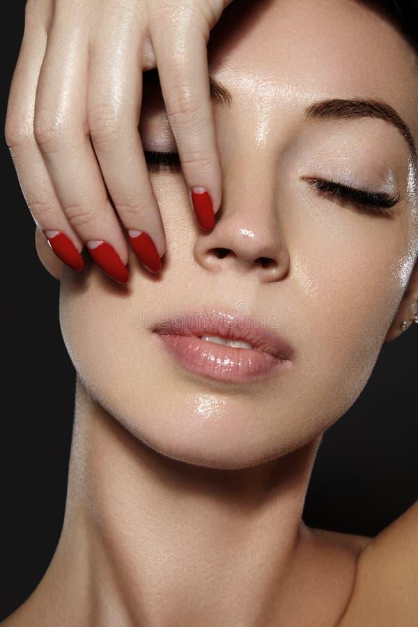 Schoonheidsmiddelen, manicure op spijkers met helder rood poetsmiddel Donkerrode lippensamenstelling en spijkerkleur royalty-vrije stock foto's