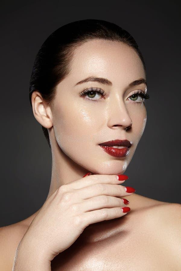 Schoonheidsmiddelen, manicure op spijkers met helder rood poetsmiddel Donkerrode lippensamenstelling en spijkerkleur royalty-vrije stock afbeelding