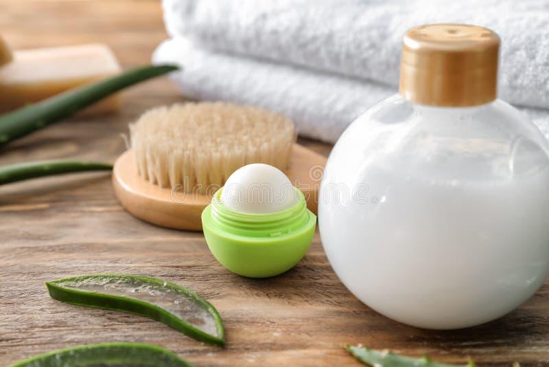 Schoonheidsmiddelen met borstel en badhanddoeken op houten lijst stock afbeelding