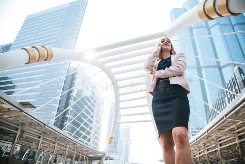 Schoonheidsonderneemster die mobiele telefoon voor het communiceren met klanten in de stad met behulp van Bedrijfs en technologie royalty-vrije stock foto's