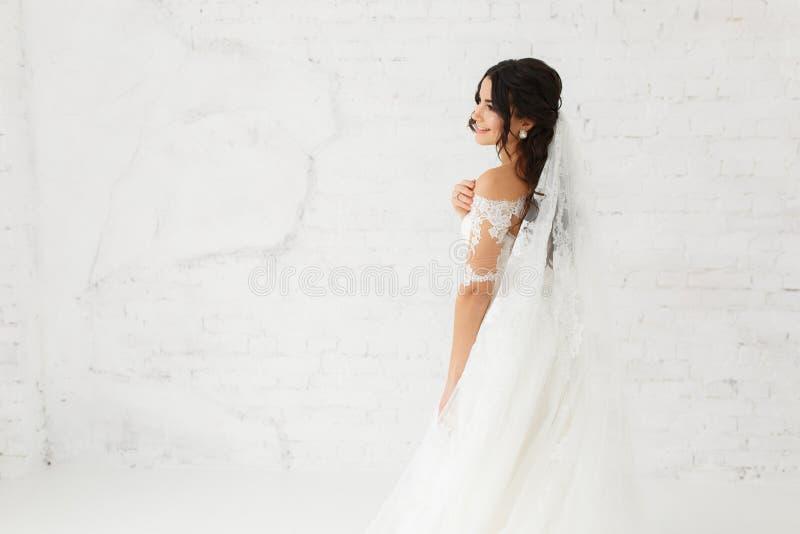 Schoonheidsportret van bruid die de kleding van het manierhuwelijk met veren met de samenstelling van de luxeverrukking en kapsel royalty-vrije stock foto's