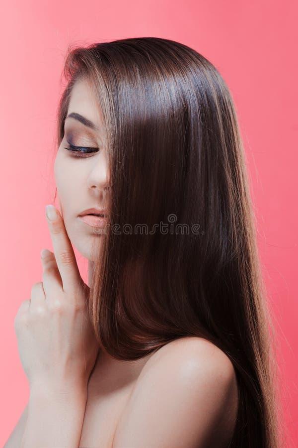 Schoonheidsportret van brunette met perfect haar, op een roze achtergrond De zorg van het haar stock afbeelding