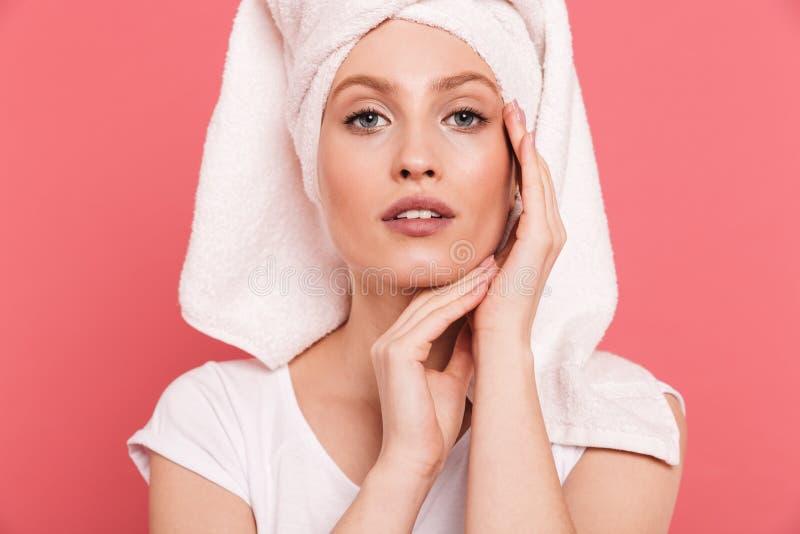 Schoonheidsportret van charmante jonge die vrouwenjaren '20 in witte handdoek na douche wat betreft haar schoon vers gezicht word royalty-vrije stock fotografie