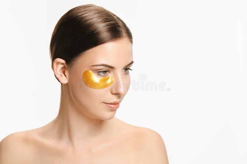 Schoonheidsportret van een aantrekkelijk meisje met een gouden flard onder het oog stock afbeeldingen