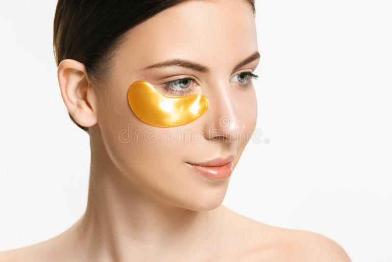 Schoonheidsportret van een aantrekkelijk meisje met een gouden flard onder het oog stock foto's