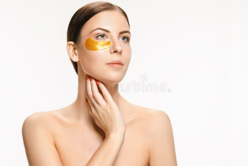 Schoonheidsportret van een aantrekkelijk meisje met een gouden flard onder het oog stock afbeelding