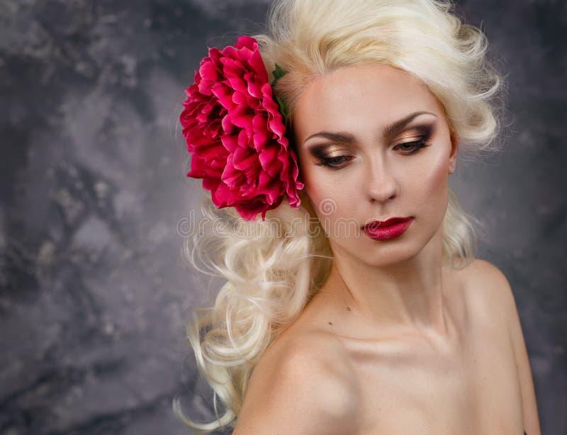 Schoonheidsportret van een blonde met een grote rode bloem in haar haar stock foto