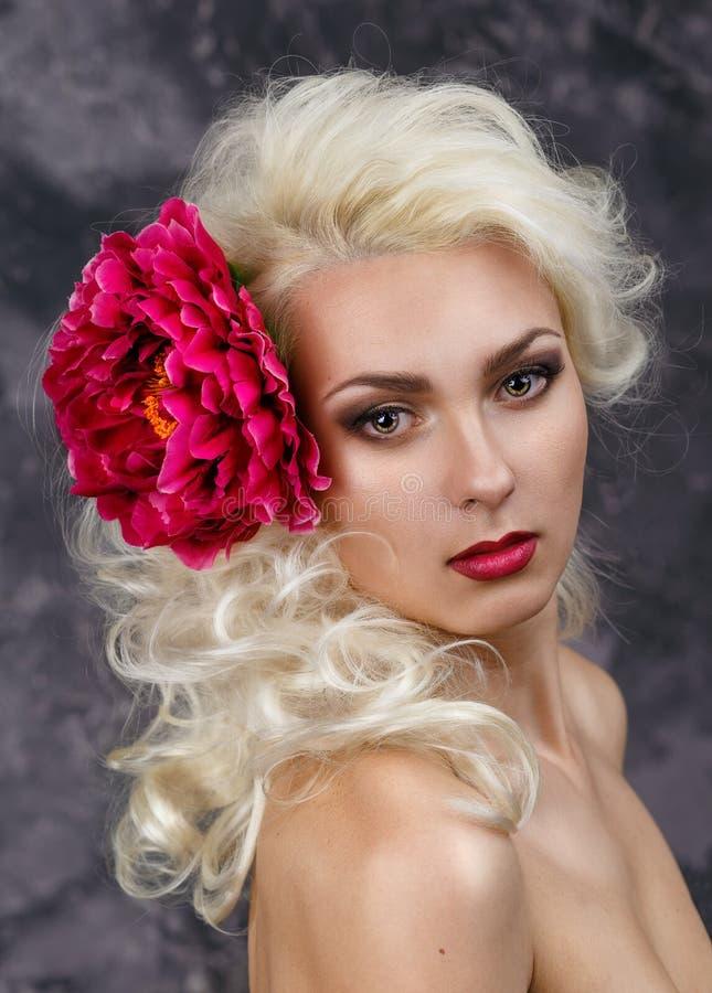 Schoonheidsportret van een blonde met een grote rode bloem in haar haar stock afbeelding