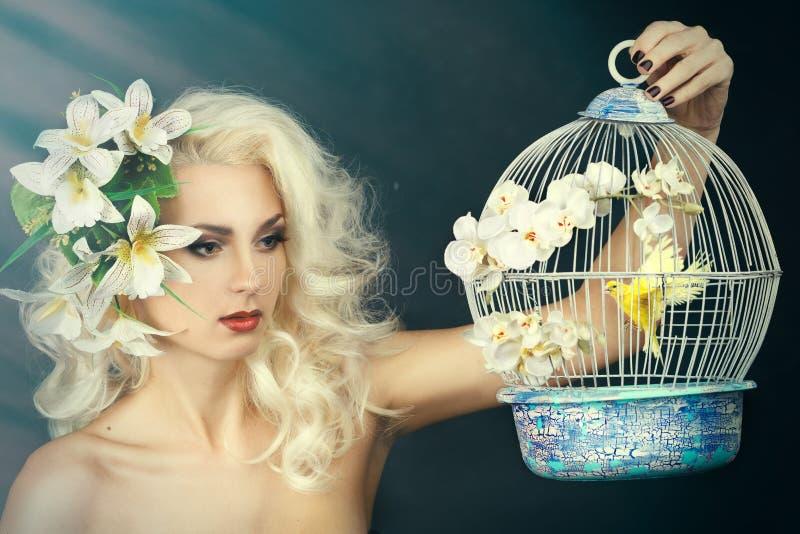 Schoonheidsportret van een meisje met een lelie in haar haar Blonde die een kooi met een vogel houden stock afbeelding