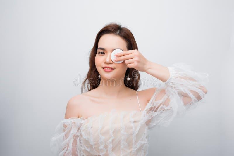 Schoonheidsportret van een vrolijke jonge topless vrouw die gezichtssamenstelling met een katoenen die stootkussen verwijderen ov royalty-vrije stock foto's