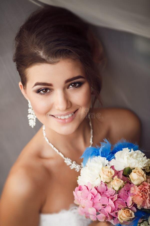 Schoonheidsportret van het jonge boeket van de bruidholding Perfecte make-up a royalty-vrije stock foto
