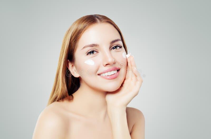 Schoonheidsportret van het leuke jonge vrouw glimlachen terwijl het toepassen van wat gezichtsroom op haar wang stock fotografie
