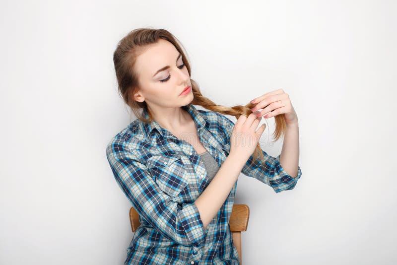 Schoonheidsportret van jonge aanbiddelijke verse kijkende blondevrouw met de hoge chaos van het broodjeshaar in blauw plaidoverhe royalty-vrije stock afbeelding