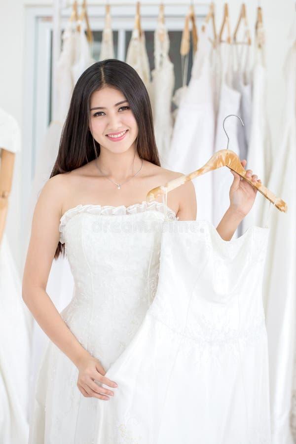 Schoonheidsportret van jonge Aziatische bruid die huwelijkskleding in huwelijkssalon kiezen van manieropslag, luxe stock fotografie
