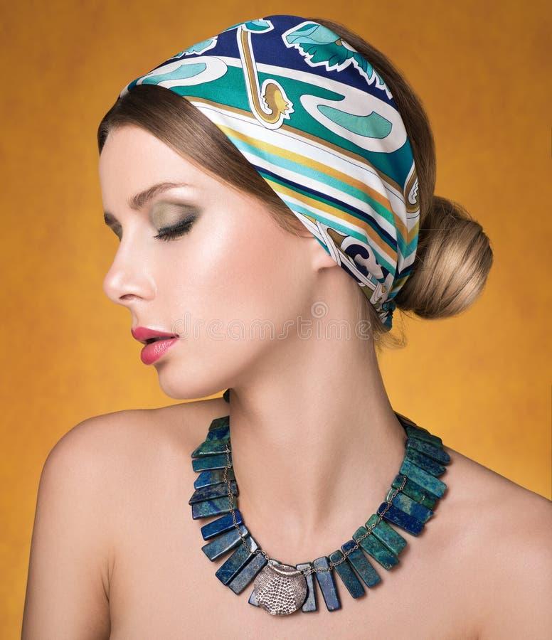 Schoonheidsportret van jonge mooie vrouw met gesloten ogen Halsband en haar met een headscarf royalty-vrije stock afbeeldingen