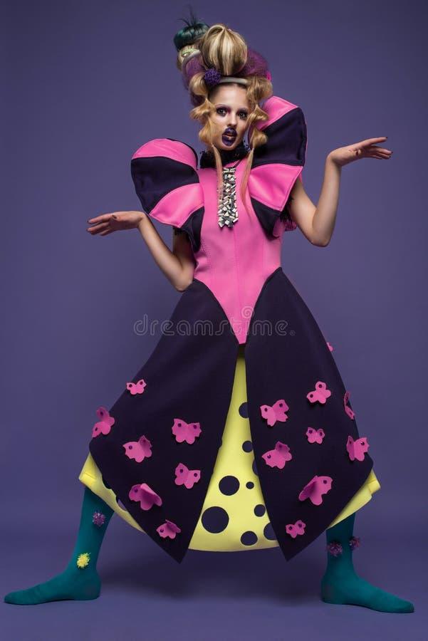Schoonheidsportret van jonge vrouw die manierkleding met creatief kapsel en heldere make-up dragen stock foto