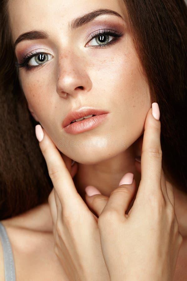 Schoonheidsportret van jonge vrouw wat betreft gezicht met vingers Brune stock fotografie