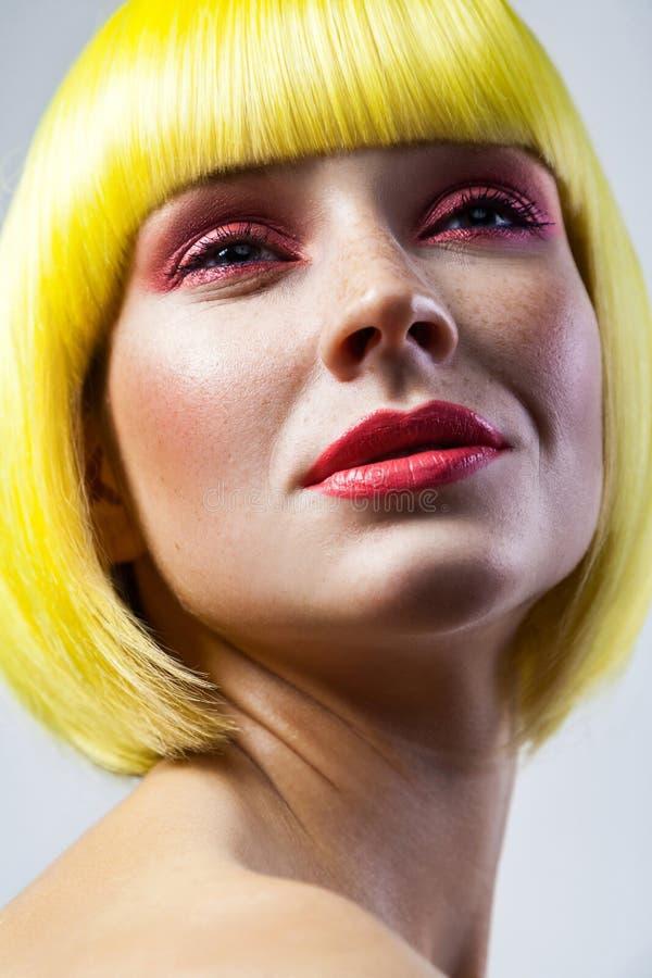 Schoonheidsportret van kalm leuk jong vrouwelijk model met sproeten, rode make-up en gele pruik stock foto's