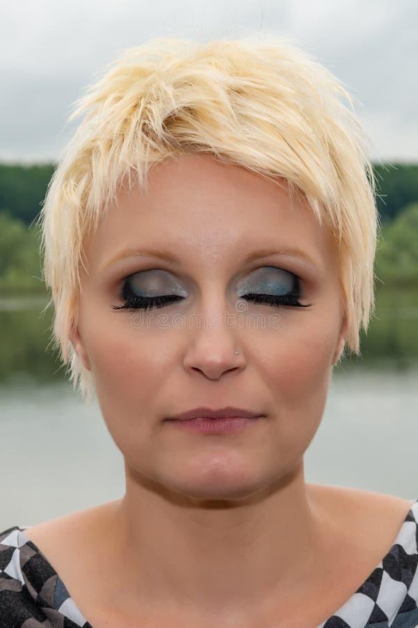 Schoonheidsportret van Kaukasisch wit meisje met kort blondiehaar in openlucht De ogenmake-up van Smokey royalty-vrije stock afbeelding