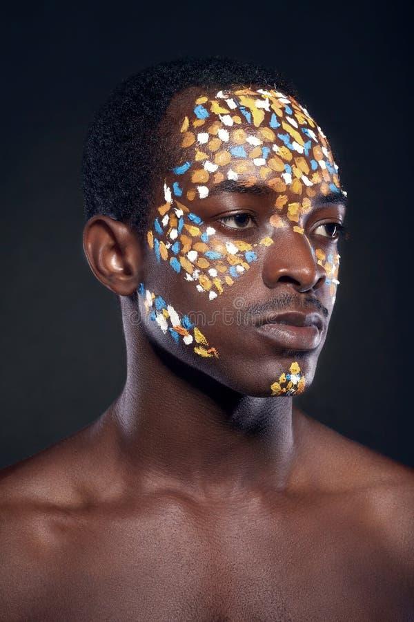 Schoonheidsportret van knap etnisch Afrikaans mannetje met creatieve ma stock foto