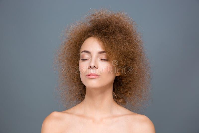 Schoonheidsportret van krullende ontspannen jonge vrouw met gesloten ogen stock fotografie