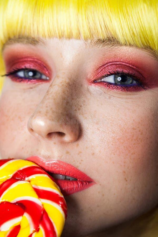 Schoonheidsportret van leuk jong meisje met sproeten, rode make-up en gele pruik die, die kleurrijke suikergoedstok op lippen hou stock fotografie