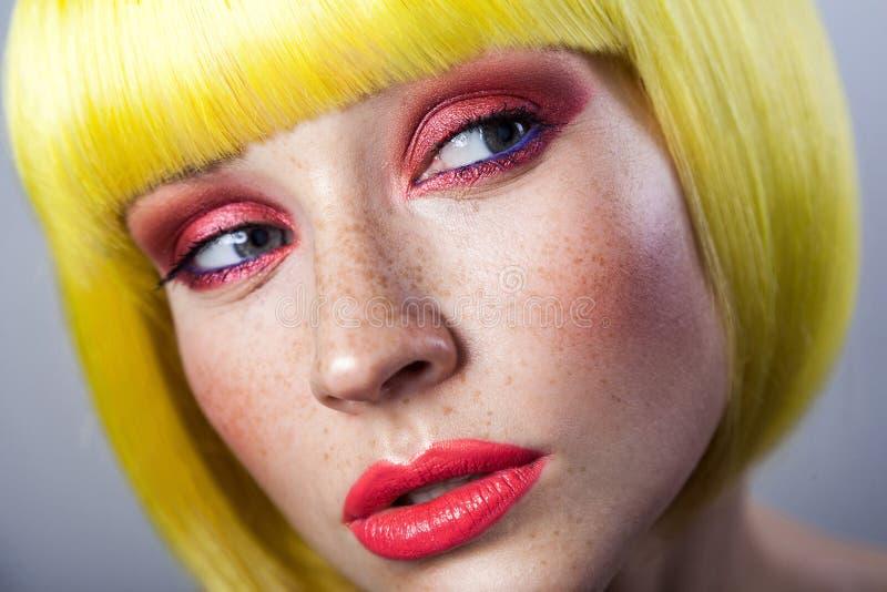 Schoonheidsportret van leuk jong vrouwelijk model met sproeten, rode make-up en gele pruik, die weg met ernstig gezicht kijken royalty-vrije stock foto's