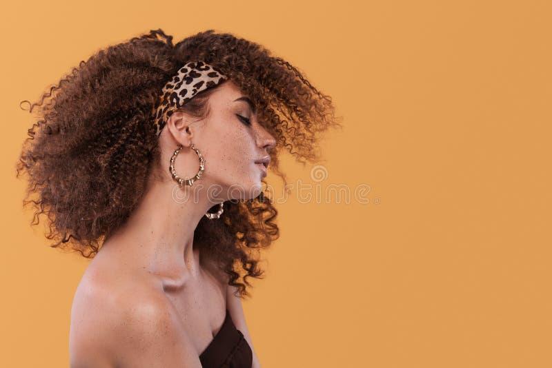 Schoonheidsportret van meisje met afrokapsel Meisje het stellen op gele achtergrond Het schot van de studio stock fotografie