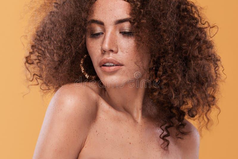 Schoonheidsportret van meisje met afrokapsel Meisje het stellen op gele achtergrond Het schot van de studio stock afbeeldingen
