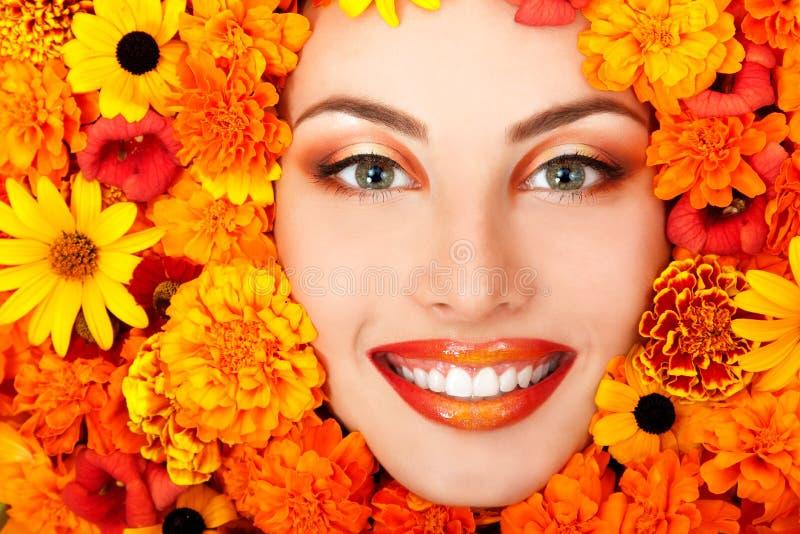 Schoonheidsportret van mooi vrouwelijk gezicht met oranje bloemenfra royalty-vrije stock afbeelding